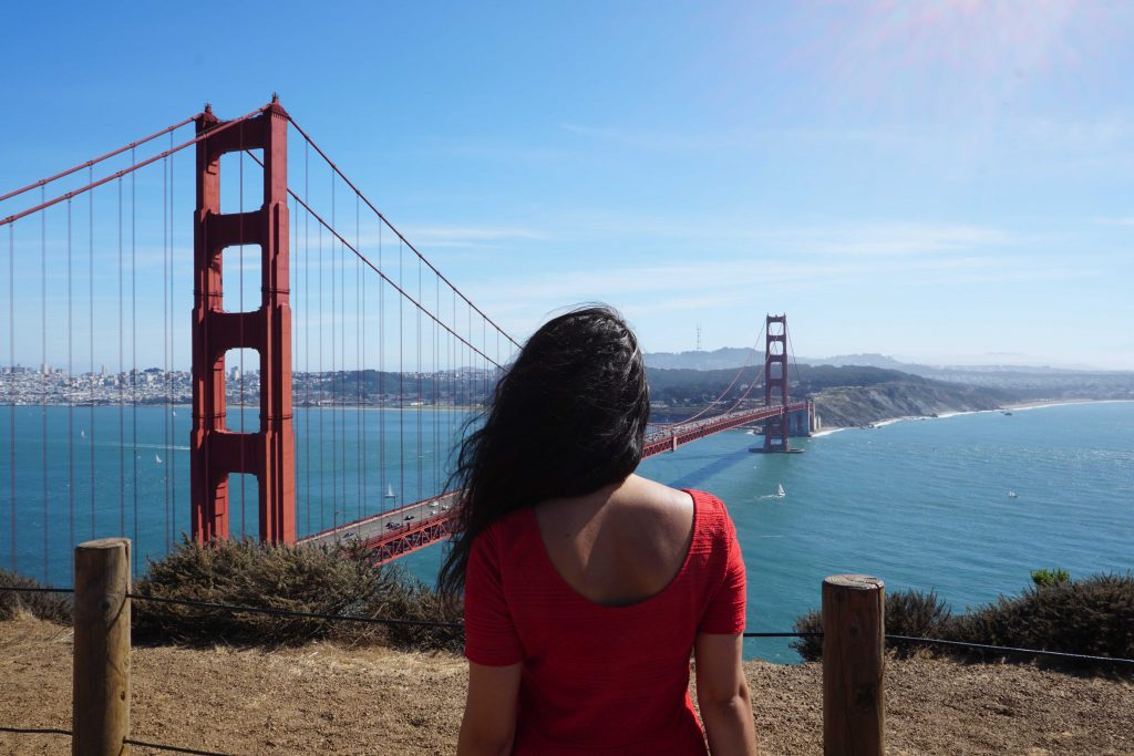 woman in red in front of the San Francisco Golden Gate Bridge Jennifer O'Brien The Travel Women