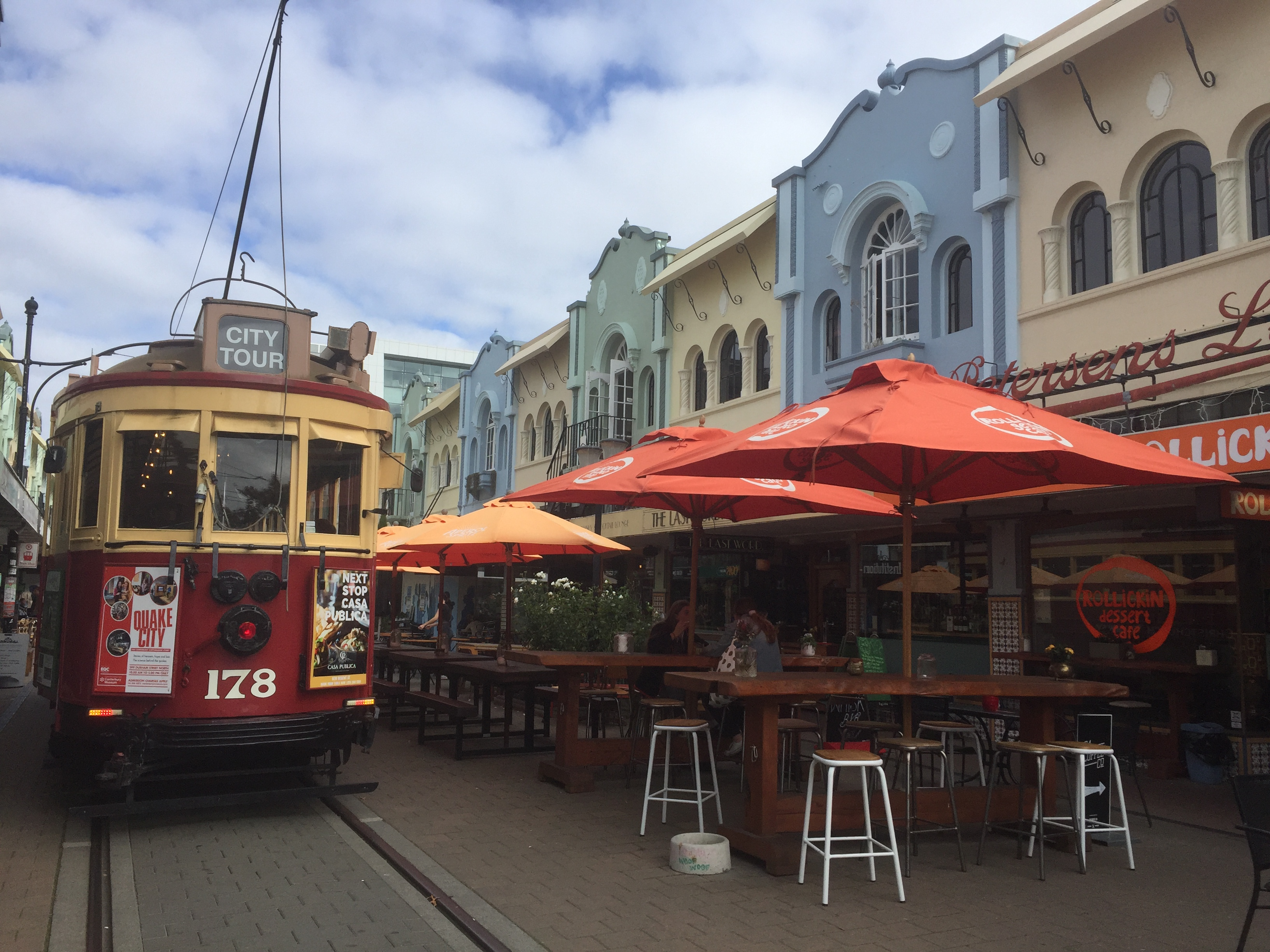 Christchurch New Regent Street NZ cable car in front of colorful umbrellas and houses