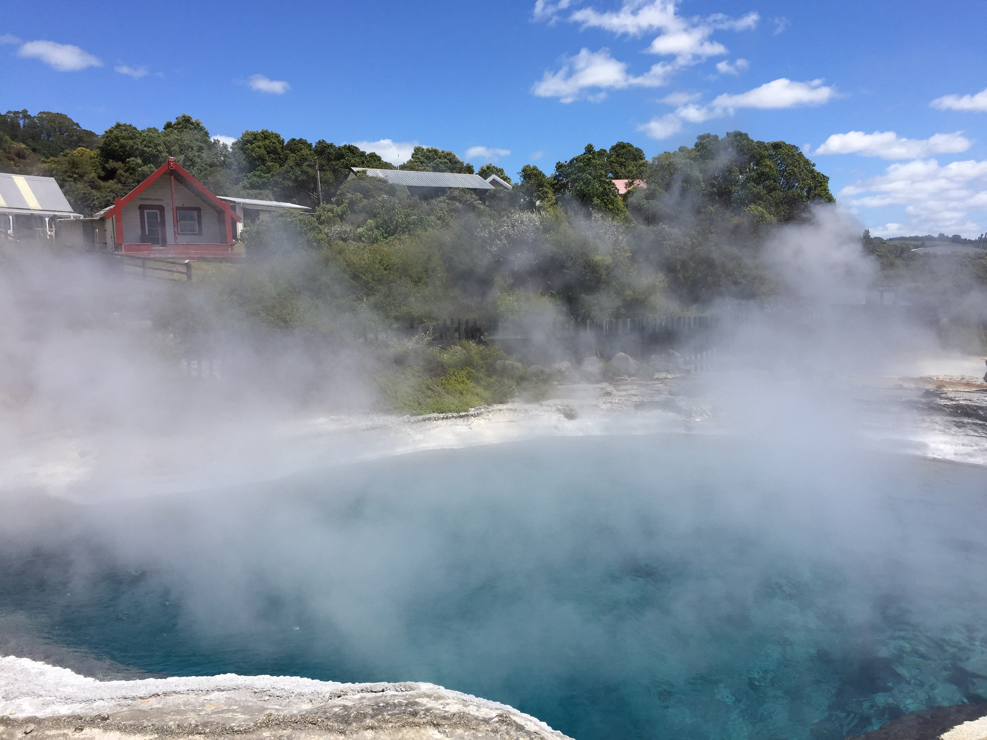 Rotorua Whakarewareawa NZ top destination hot springs steam over blue water in front of red house