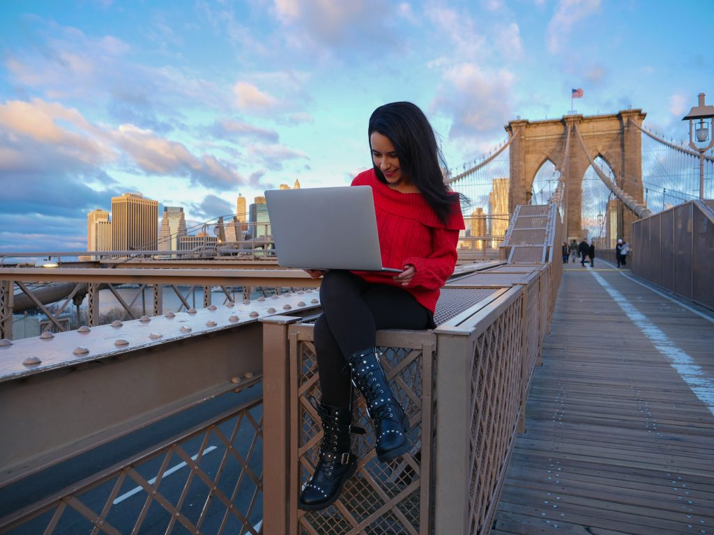 Brooklyn Bridge NYC laptop girl in red on computer video editing